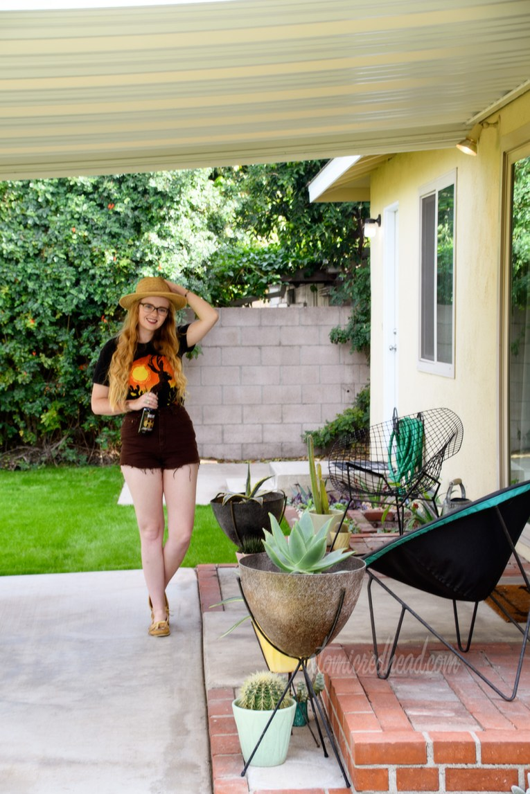 Myself standing on our patio, wearing a black t-shirt with a jackalope on it, brown shirts, and a woven straw hat. Planters scatter the patio with various cacti and succulants.