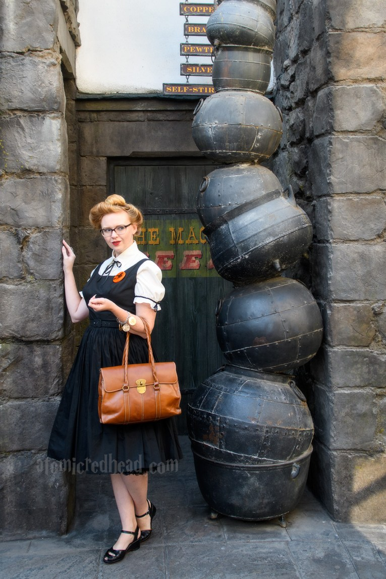A stack of cauldrons marks the entrance to the Magical Neep, a shop in Hogsmeade, wearing a white blouse under a black dress. A brooch of a witch on a broom worn on my left, and carrying a tan leather satchel stye purse.