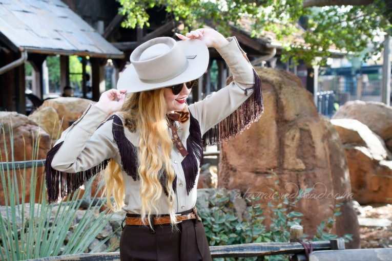 Myself, standing in front of Big Thunder Railroad, wearing a tan cowboy hat, a tan western wear shirt with dark brown fringe, and embroidered flowers, a dark brown string tie with painted flowers, and dark brown western pants with orange flowers embroidered near the bottom.