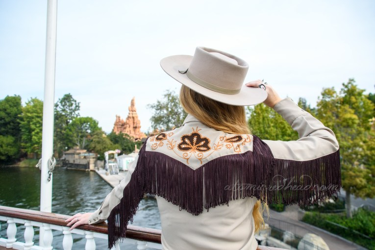 A view of my back, aboard the Mark Twain riverboat, with Big Thunder Mountain in the distance. The back of my western wear shirt features dark fringe, and dark brown flowers, edged in gold tone embroidery.