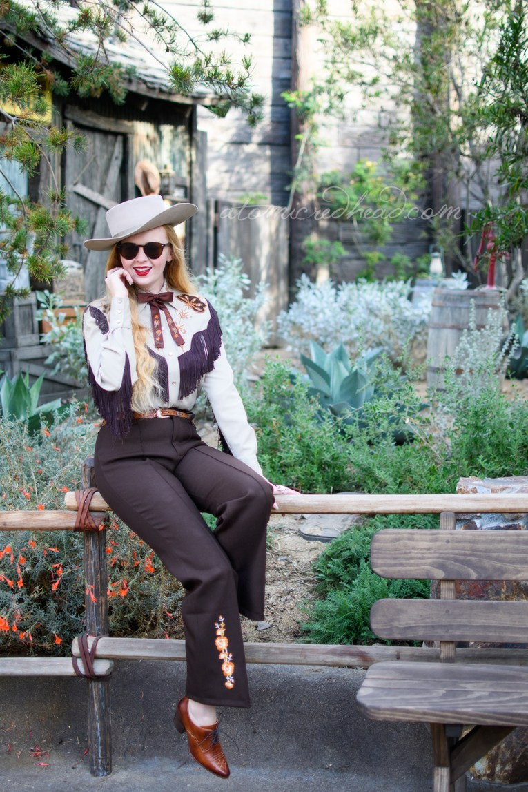Myself, sitting on a fence in front of a little shack surrounded by cacti and succulents, wearing a tan cowboy hat, a tan western wear shirt with dark brown fringe, and embroidered flowers, a dark brown string tie with painted flowers, and dark brown western pants with orange flowers embroidered near the bottom.