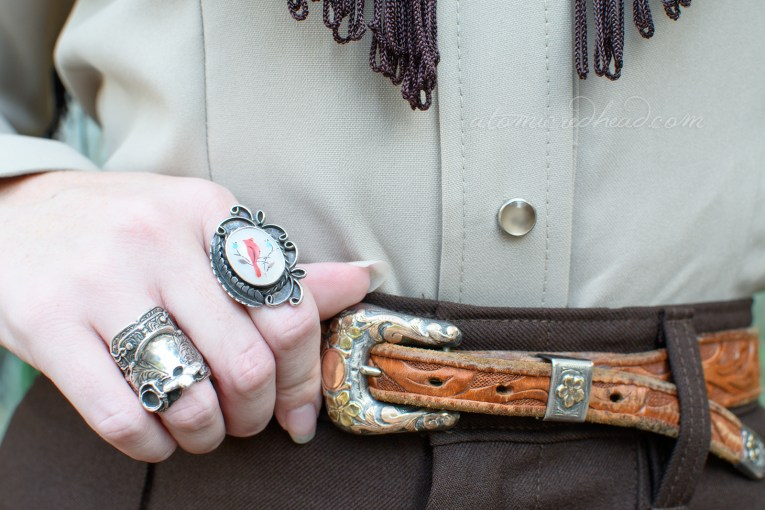 Close-up of my belt, which is gold and silver and features flowers on the buckle, my hand sits atop it with a mother of pearl ring inlayed with a coral cardinal, and on another finger a silver saddle ring.