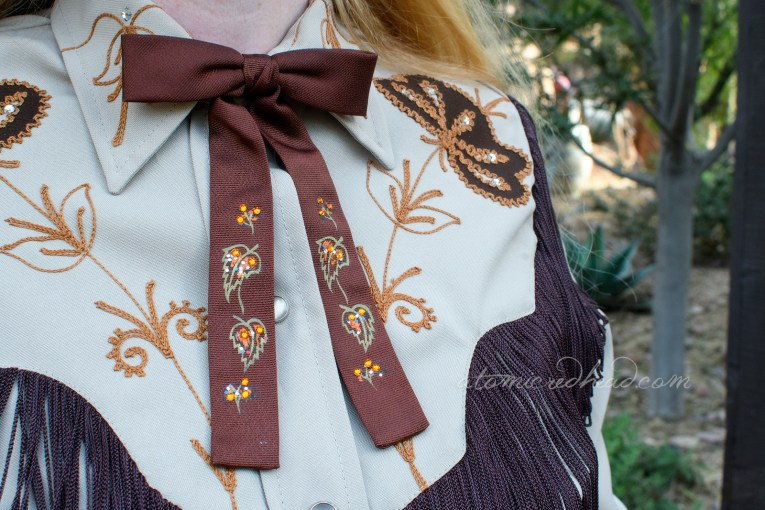Close-up of my string tie, dark brown, with painted flowers and leaves in gold, and orange rhinestones dotted on it.
