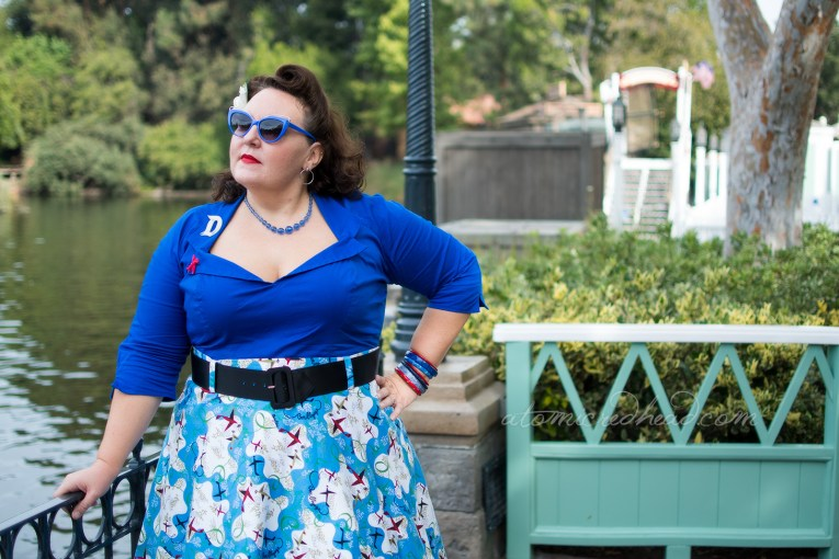 Dor stands on the banks of the Rivers of America, wearing a bright blue top, with a white D brooch, and red airplane brooch, and a skirt of blue and white with small air