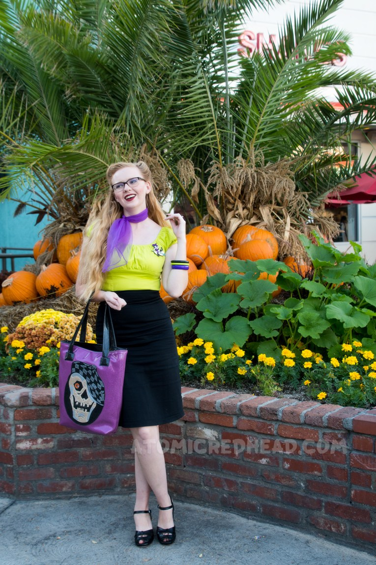 Myself, standing in front of a planter of orange and yellow flowers, and pumpkins, wearing a lime green peasant top, black pencil skirt, and purple scarf, and a purple bag with a skull wearing a cap.