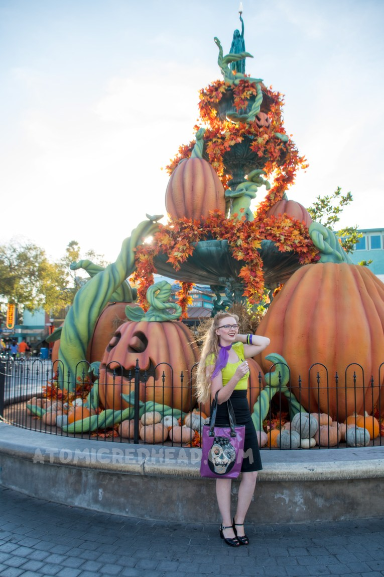 Myself, standing in front of a large fountain with big pumpkins sitting in it, wearing a lime green peasant top, black pencil skirt, and purple scarf, and a purple bag with a skull wearing a cap.