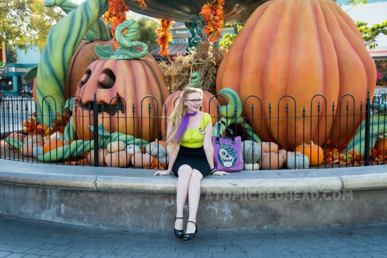 Myself, sitting in front of a large fountain with big pumpkins sitting in it, wearing a lime green peasant top, black pencil skirt, and purple scarf, and a purple bag with a skull wearing a cap.