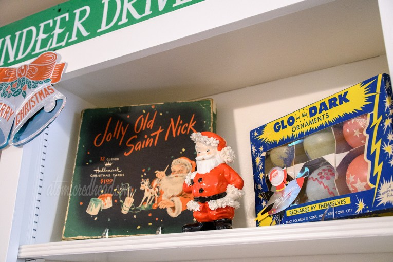 """A vintage card box features Santa painting toys, next to it stands a ceramic Santa, and next to it is a box of """"Glo in the Dark"""" ornaments, the box is blue and feature bright yellow stars."""