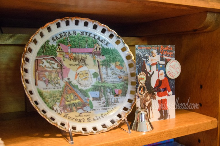 """A vintage ceramic plate for Santa's Village in Sky Forest, California, featuring images of storybook houses. Next to it a souvenir bell from Santa's Village, a postcard of Santa at Santa's Village, and a button reading """"Santa's Village Guest"""""""