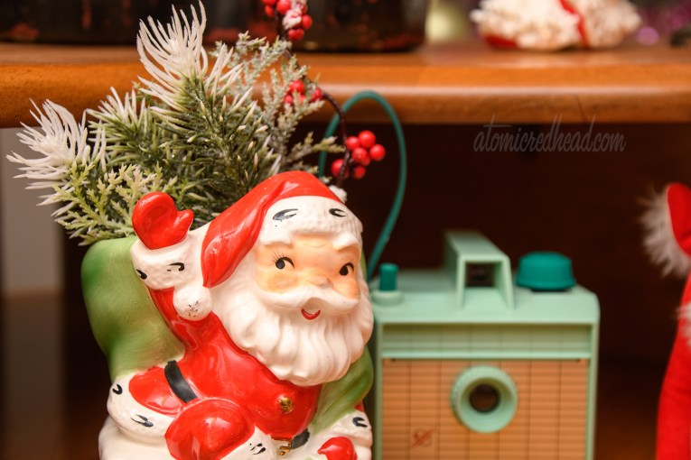 A ceramic planter features Santa climbing out of a chimney, peeking out of the top is a bundle of pine sprigs.