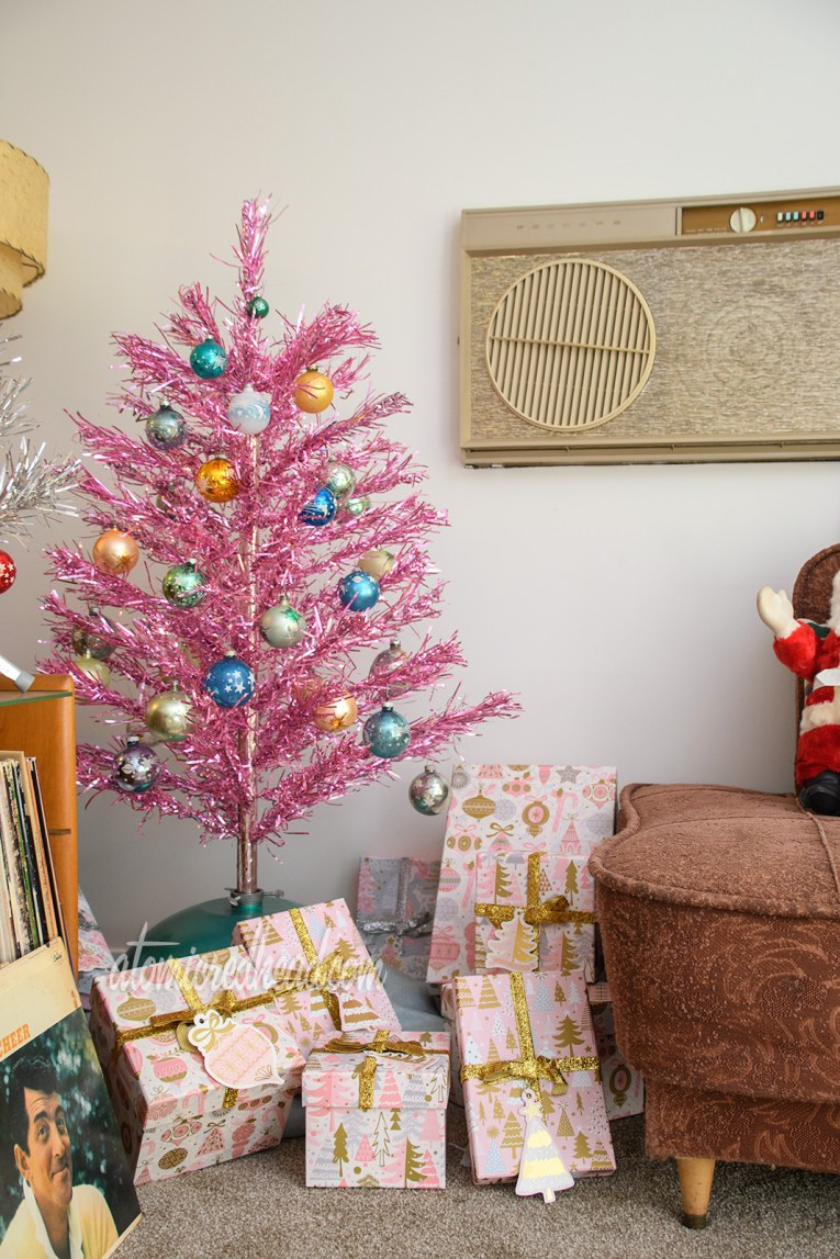 A small pink aluminum tree stands against a wall, with blue, gold, and green glass ornaments featuring moons and stars. Under it are pink and gold presents.
