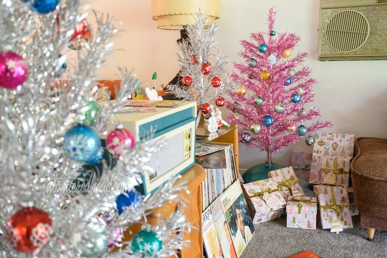 In the foreground a silver aluminum tree, next to it is a wood and glass console with a teal and cream record player and a small aluminum tree atop, and in the background a pink aluminum tree.