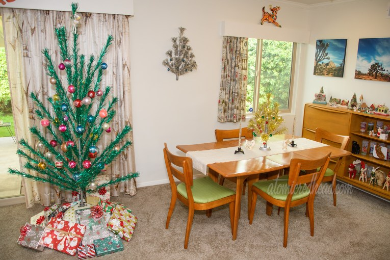 The green aluminum tree with various colored ornaments stands on the left with our dining room table on the right. Atop the dining room table is a small, one foot gold aluminum tree. Hanging on the wall is a small half aluminum tree, designed to hang on the wall.