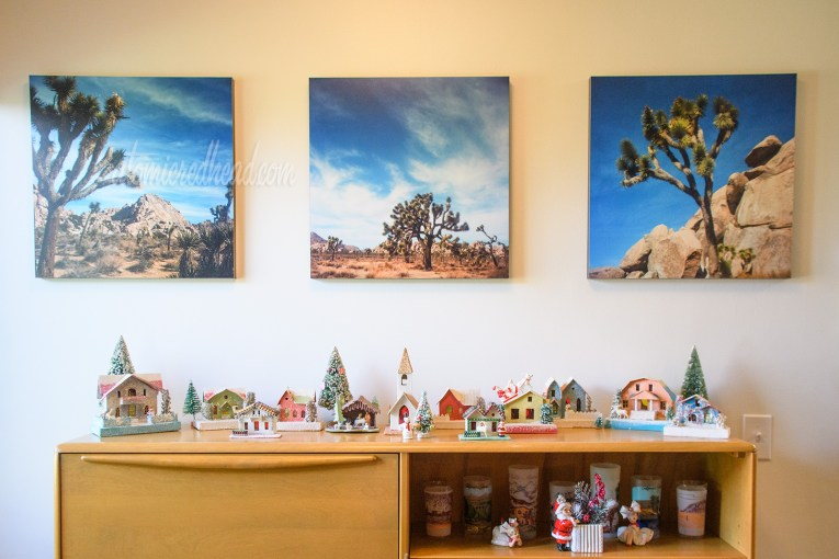 Atop a secretary features small, vintage cardboard houses. Hanging above a trio of prints of Joshua Tree.
