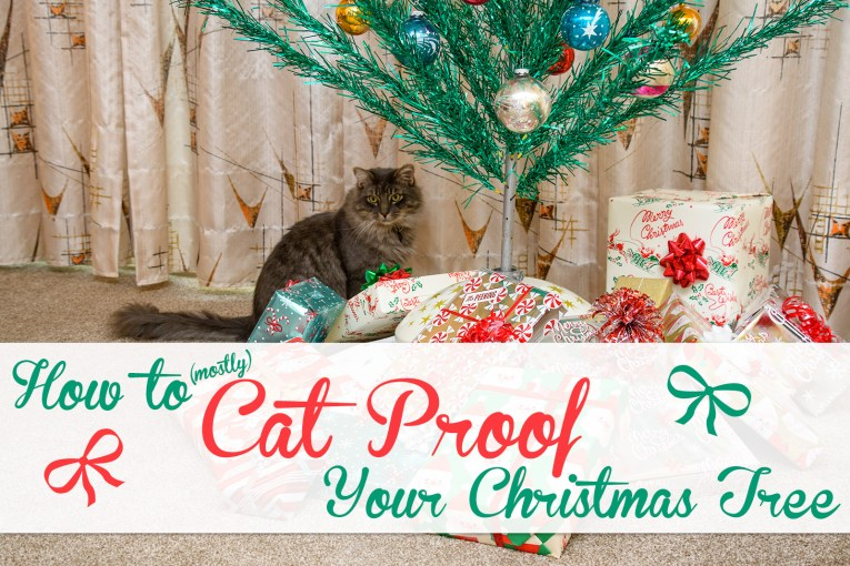 "A fluffy grey cat sits under a green aluminum tree surrounded by presents. Text overlay reads ""How to (mostly) Cat Proof Your Christmas Tree"""