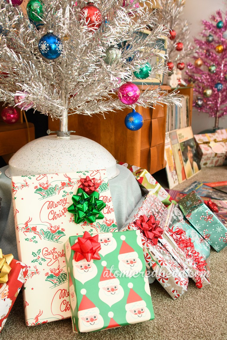 A large pile of presents sit under a silver aluminum tree that has been elevated on a platform.