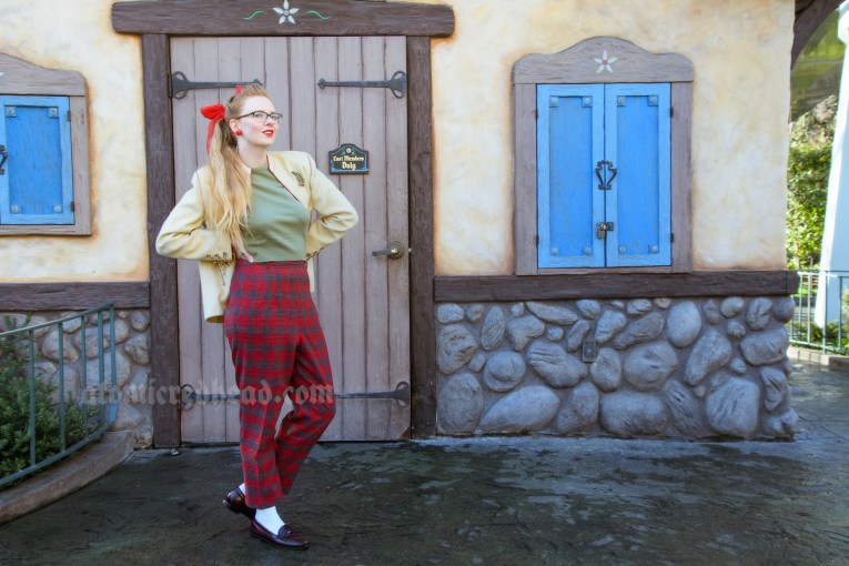 Myself standing in front of a Swiss Alps inspired building, wearing a cream jacket with a small D shaped brooch pinned to it, and a green sweater, and red and grey plaid pants.