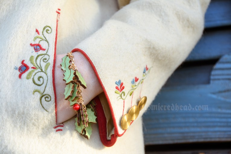 Detail of the red, green, and blue embroidery on the cuff and near the pocket, and my wood and bead holly themed charm bracelet.