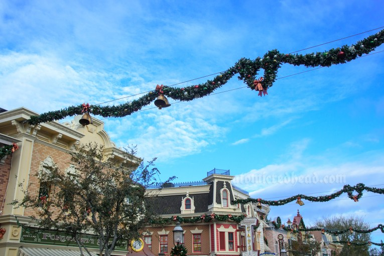 Disneyland's Main Street, decorated for the holidays with garlands and in the middle a wreath in the shape of Mickey.