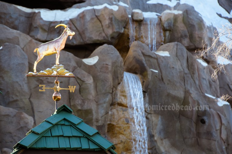 A waterfall cascades down the Matterhorn, and a small weathervane of a goat points to the right.