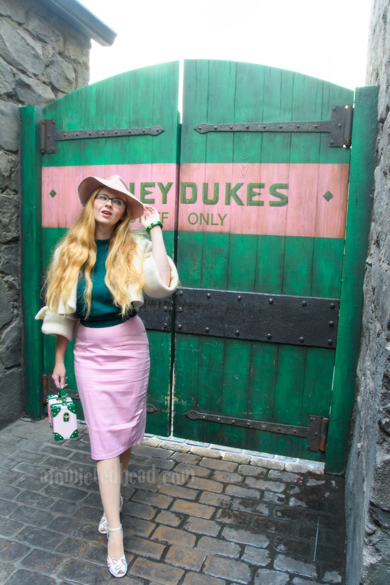 "Myself standing in front of a large green door with a large pink stripe across it which reads ""Honeydukes Staff Only."" I'm wearing a pink fedora, white bolero jacket, green sweater, pink skirt, and carrying a pink, white, and green purse featuring Honeydukes treats."