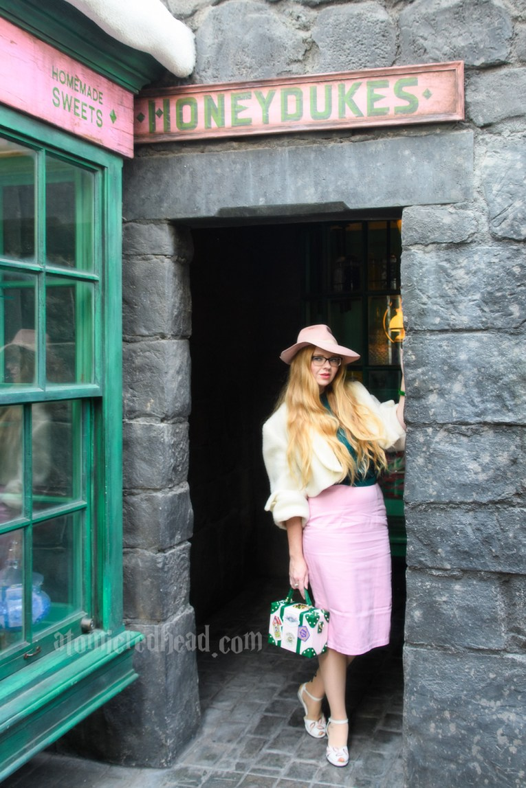 Grey stones make up the buildings of Hogsmeade, a small doorway opens into the back of the shop. I'm wearing a pink fedora, white bolero jacket, green sweater, pink skirt, and carrying a pink, white, and green purse featuring Honeydukes treats.