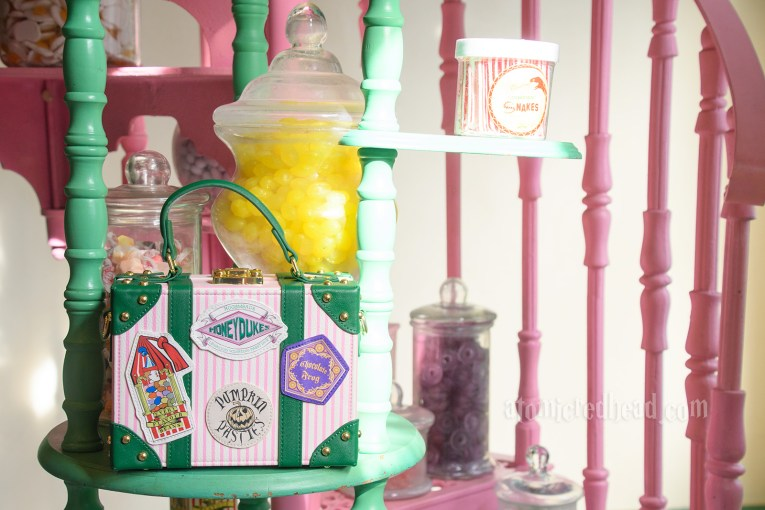 Inside Honeydukes. A pink and green spiral staircase rises upwards. Sitting on a step is my purse, which is white and pink stripes, with corners edged in green. It features travel style stickers with Bernie Bot's Every Flavor Beans, Chocolate Frogs, Pumpkin Pasties, and Honeydukes.