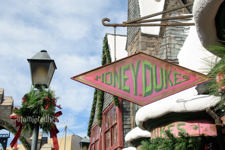 The diamond shaped Honeydukes sign hangs among snow covered shop roofs.