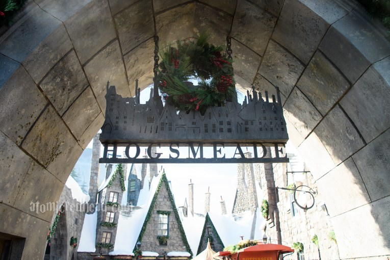 The sign welcoming you to Hogsmeade, featuring silhouettes of the roofline, and a small wreath hangs on it.