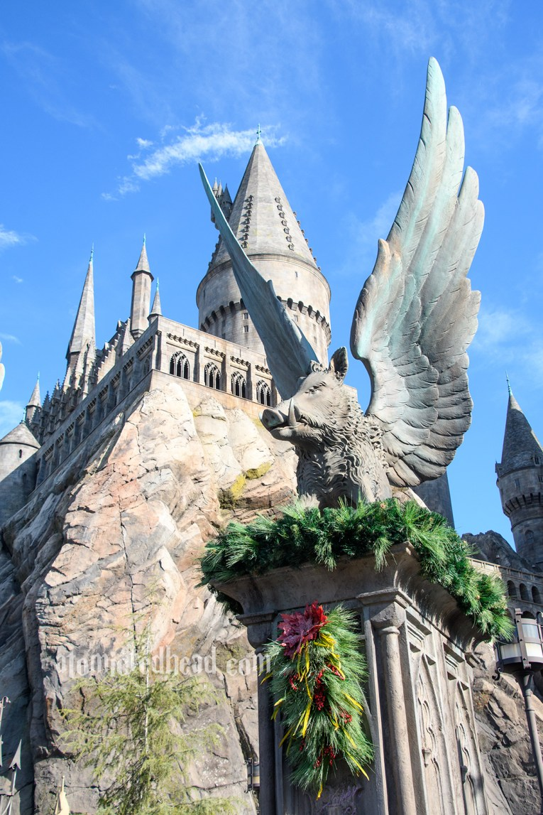 The wings boars of Hogwarts stand outside the castle, which towers over Hogsmeade.