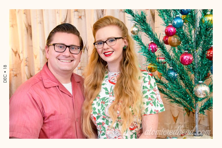 Patrick and myself seated by a green aluminum Christmas tree. Patrick wears a red button down shirt, and I wear a dress featuring a print of Santa heads and holly on a white background.