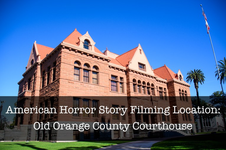"""A red stone building with arches in the middle stands tall with text overlay reading """"American Horror Story Filming Location: Old Orange County Courthouse"""""""