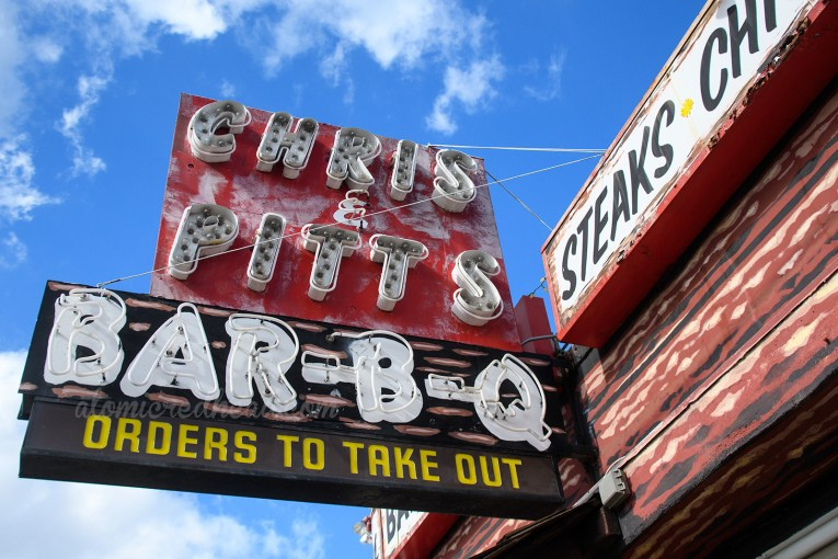 "Close up of the sign, the upper half is red, and in white letters reads ""Chris * Pitt's"" and below the sign is black with white letters that read ""Bar-B-Q"""