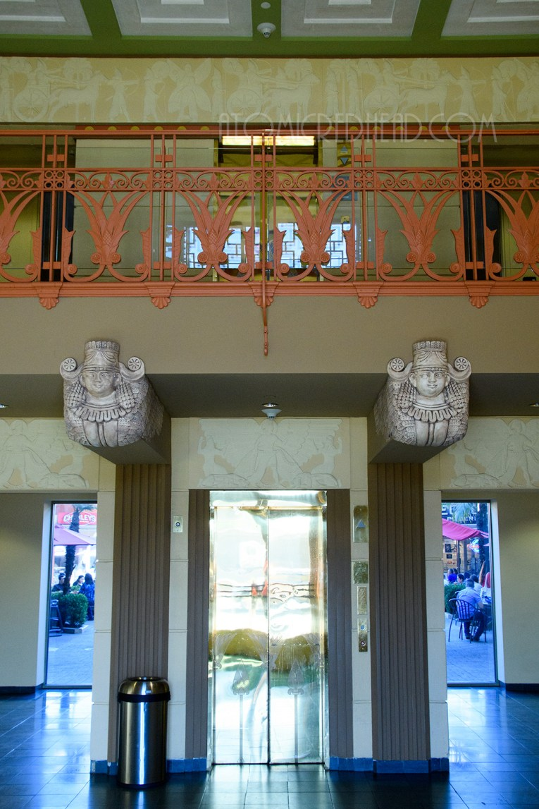 Just inside the building is a central golden elevator, with a balcony above. Holding the balcony are busts of women. The balcony features an iron railing that is painted orange and features lotus flowers.