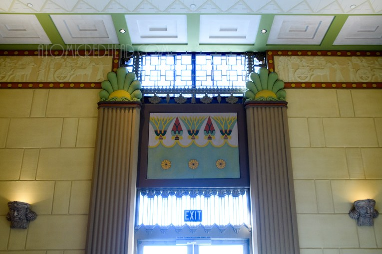 The front doors from the inside, with columns on either side of the door, and a mural of lotus flowers above.