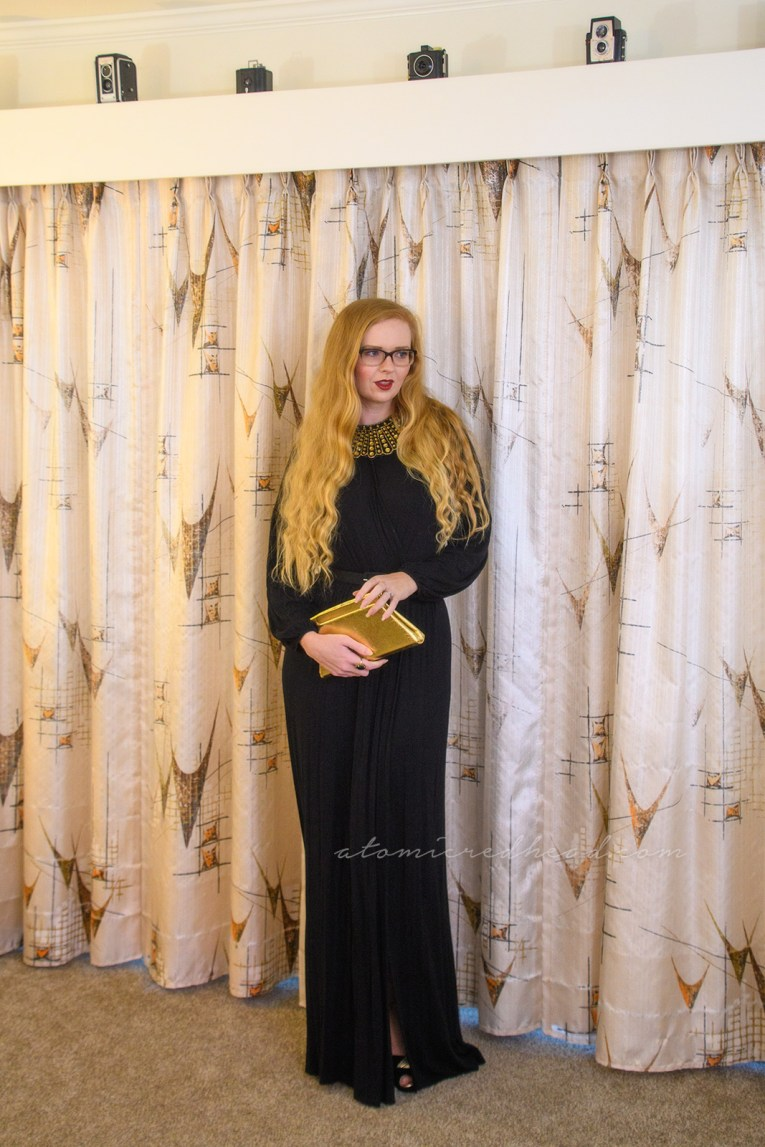 Myself wearing a long sleeve, full length black dress, with a slit up the side, wearing an art decor fan style necklace of gold rhinestones, paired with a gold trapezoid shaped clutch.