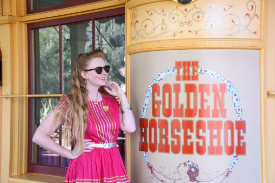 Myself standing in front of the Golden Horseshoe Saloon, wearing a magenta dress with gold and silver ric-rac, a silver belt, and silver moccasins.