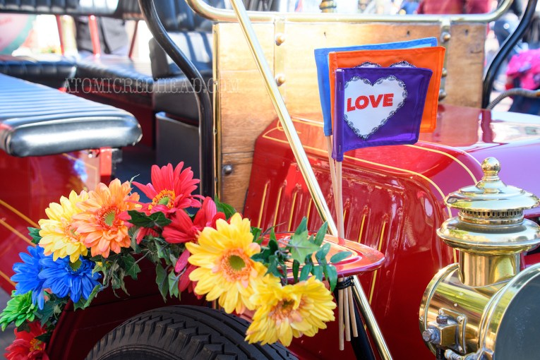 "Colorful flowers and a trio of flags featuring hearts reading ""love"" are attached to the fender of one of the horseless carriages of Main Street."