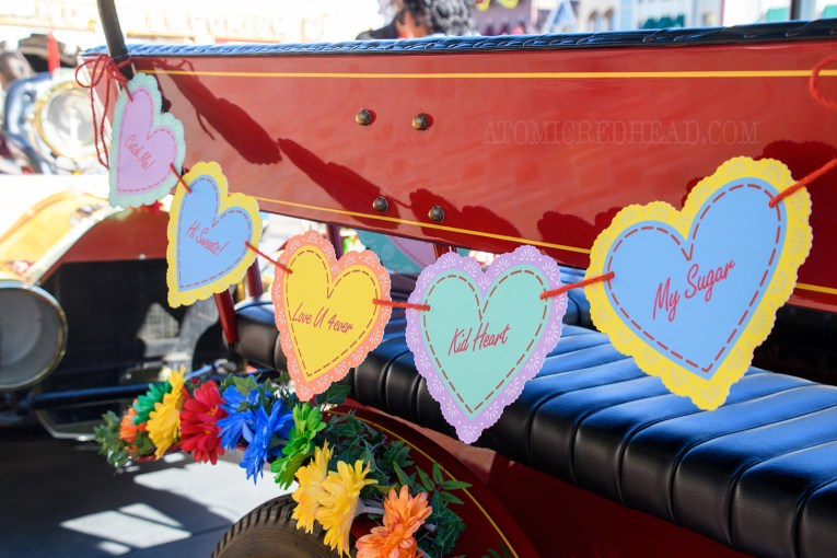 """A garland of different colored hearts hang on one of the horseless carriages of Main Street, reading """"Catch Me"""" """"Hi Sweets"""" and more."""