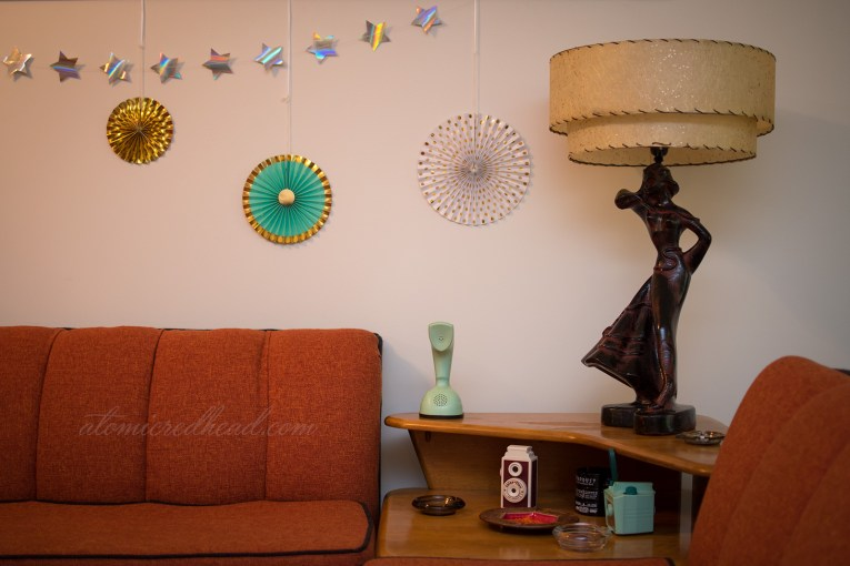 An orange and black couch sits against a wall, and turquoise, gold, and white fan wheels hang along the wall.