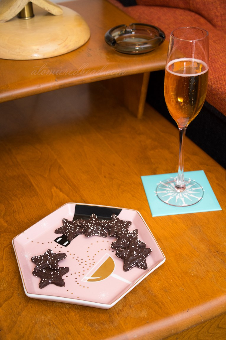 A champagne flute stands next to a small dish that features a champagne glass being filled by a black bottle.