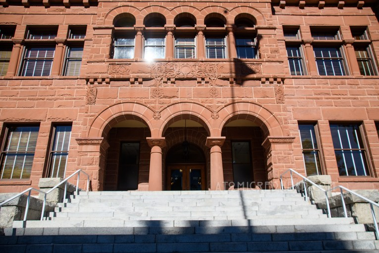The Old Orange County Courthouse, a large, three-story building made of red sandstone. It features three small arches in the center mark the entrance. Three gables top the roofline.