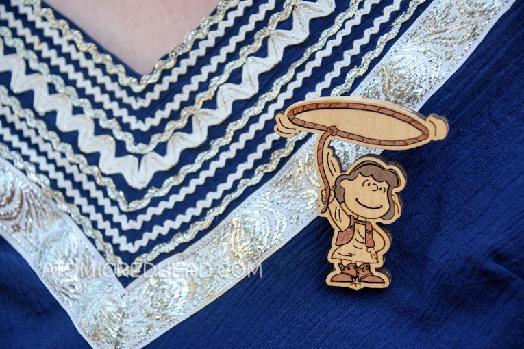 Close-up of my brooch, which is laser cut wood of cowgirl Lucy with a lasso above her head.
