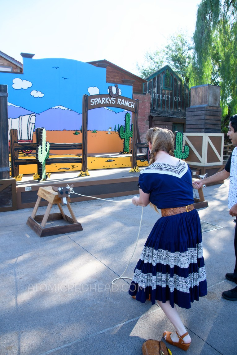 """Myself, in front of a Peanuts style backdrop of a desert scene, lassoing a """"steer"""" made from a saw horse, wearing a navy colored patio set with silver ric-rac trim, and a tooled leather belt, purse, and shoes."""