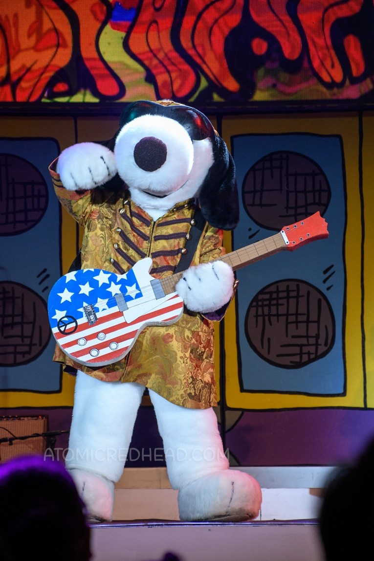 """Snoopy arrives on stage as """"Jimi Hound-rix"""" during the Woodstock's Music Festival stage show."""