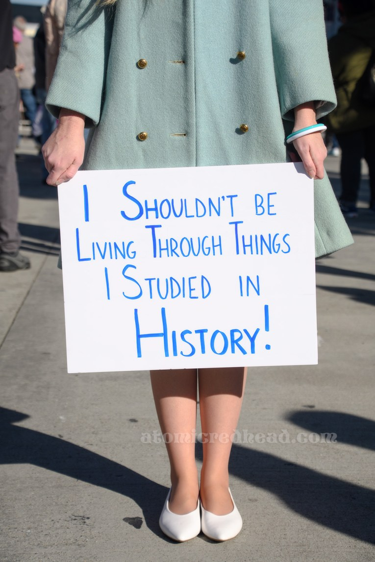 "A view, waist down, of me holding my sign which reads ""I Shouldn't Be Living Through Things I studied in History!"" in blue."