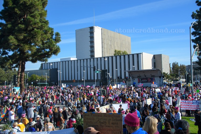 A crowd of marchers meet in the middle of downtown Santa Ana, a scattering of pink dots the crowd.