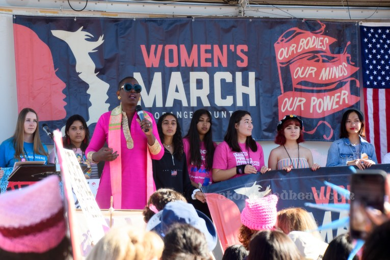 "A speaker takes to the stage, wearing all pink. She is standing in front of a series of young women, many of them also wearing pink. Behind them a large navy banner reads ""Women's March Our Bodies, Our Minds, Our Power"" and features profiles of women in pink and white."