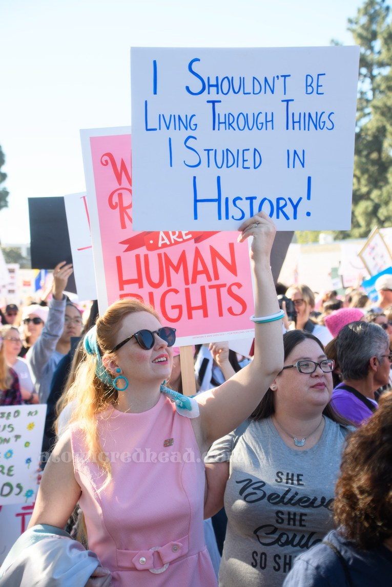 """Myself, wearing a pink mini dress and blue scarf carrying a sign reading """"I Shouldn't Be Living Through Things I Studied in History"""" along side my friend Kaitlyn who wears a shirt reading """"She Believed She Could So She Did"""" and carrying a pink sign reading """"Women's Rights are Human Rights"""""""