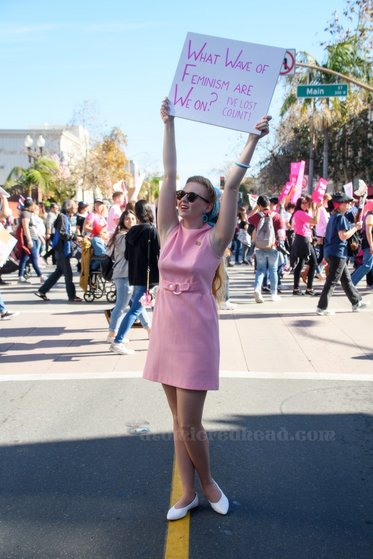 "Myself standing in a pink mini dress holding a sign reading ""What Wave of Feminism Are We On? I've Lost Count"""